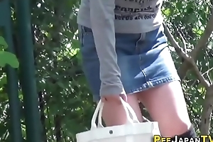 Asian mollycoddle peeing outdoor